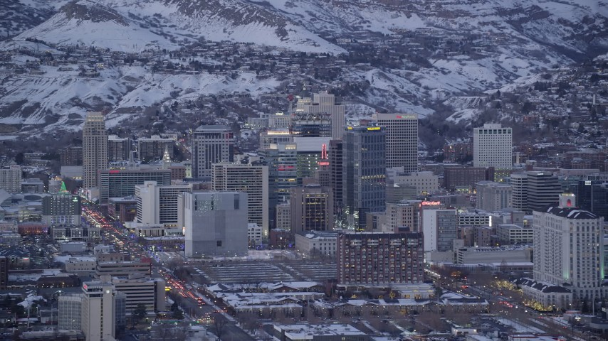6K stock footage aerial video of Downtown SLC buildings with winter snow on rooftops at twilight, Utah Aerial Stock Footage | AX128_032