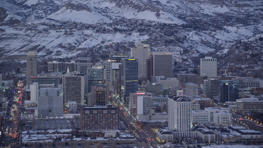 6K stock footage aerial video of Main Street and Downtown Salt Lake City, Utah buildings with winter snow at twilight Aerial Stock Footage | AX128_033