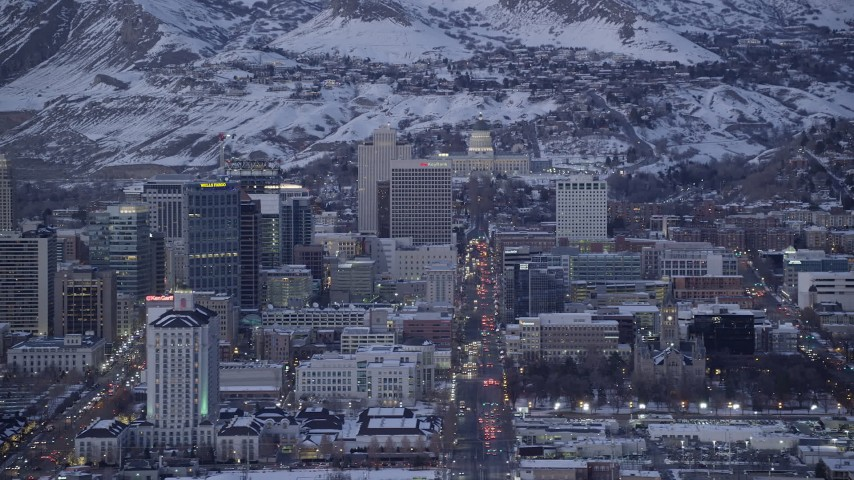 6K stock footage aerial video of passing State Street through Downtown Salt Lake City to capitol building with winter snow at twilight, Utah Aerial Stock Footage | AX128_034