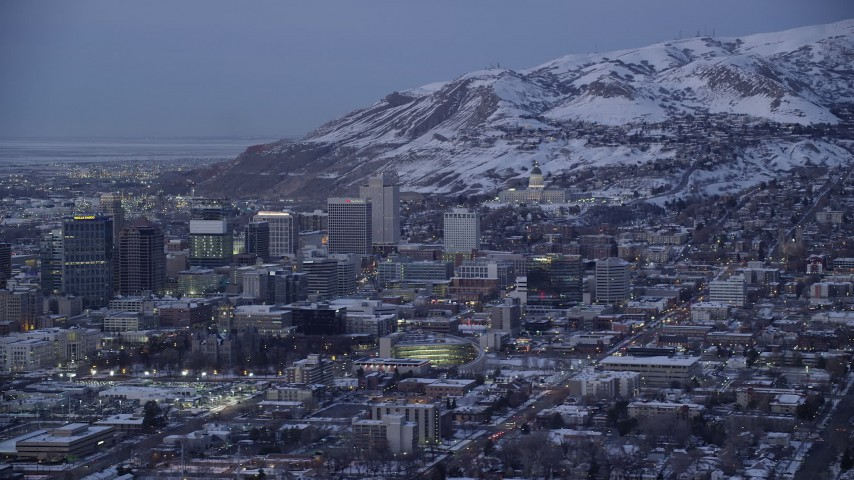 6K stock footage aerial video of Utah State Capitol and downtown with winter snow seen from southeast of Salt Lake City at twilight Aerial Stock Footage | AX128_036