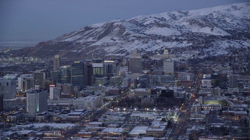 6K stock footage aerial video orbit State Street in Downtown Salt Lake City, with view of the capitol and winter snow at twilight, Utah Aerial Stock Footage | AX128_037