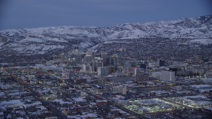Wide Orbit of Downtown SLC near Snowy Mountains at twilight Aerial Stock Footage | AX128_040