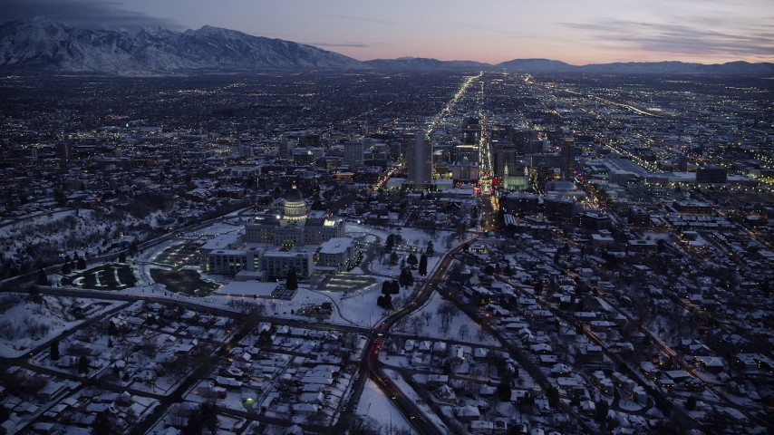 6K stock footage aerial video of circling north around the capitol and Downtown Salt Lake City with winter snow at twilight, Utah Aerial Stock Footage | AX128_051