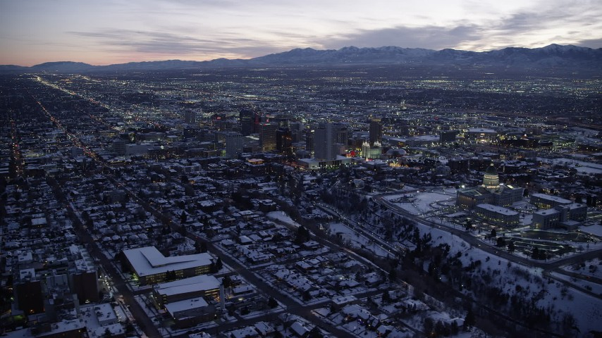6K stock footage aerial video orbit northeast of Downtown Salt Lake City and the Utah State Capitol with winter snow at twilight Aerial Stock Footage | AX128_053