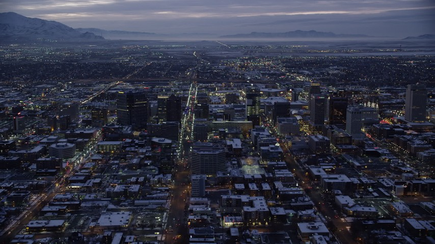 6K stock footage aerial video orbit wide streets and buildings on east side of Downtown SLC with winter snow at twilight, Utah Aerial Stock Footage | AX128_058