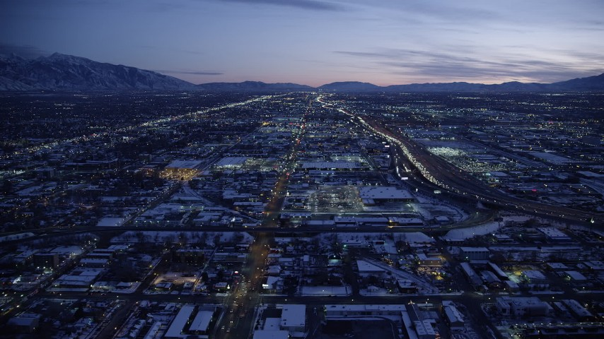 6K stock footage aerial video approach shopping center and Interstate 15 with winter snow at twilight, Salt Lake City, Utah Aerial Stock Footage | AX128_065