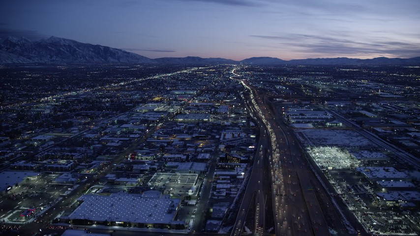 6K stock footage aerial video fly over I-15 and shopping centers with winter snow at twilight, Salt Lake City, Utah Aerial Stock Footage | AX128_067