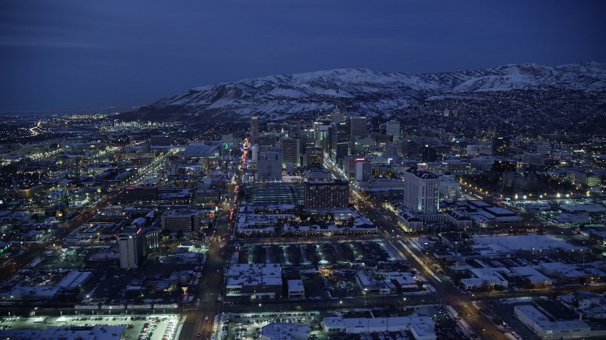 6K stock footage aerial video approach hotels on Main Street in Downtown SLC with winter snow at night, Utah Aerial Stock Footage | AX128_071