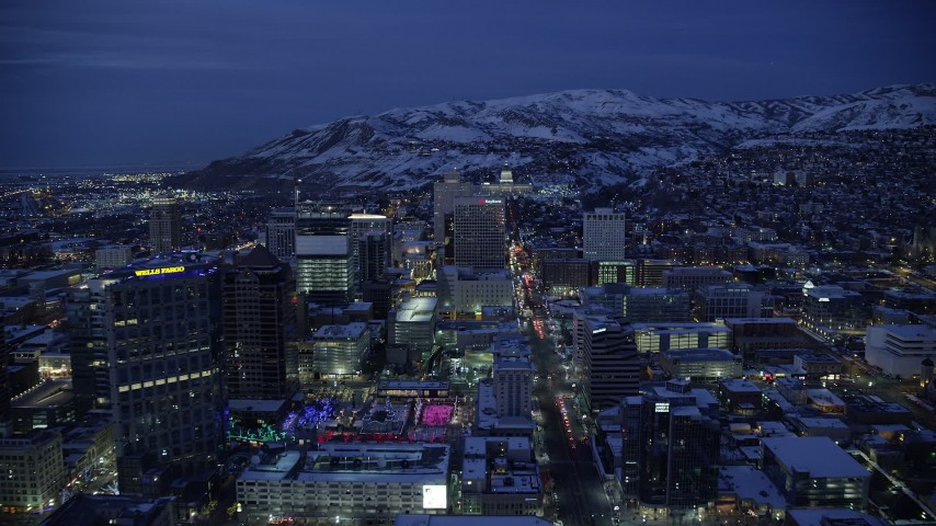 6K stock footage aerial video of following State Street through Downtown SLC and approach capitol with winter snow at night, Utah Aerial Stock Footage AX128_073