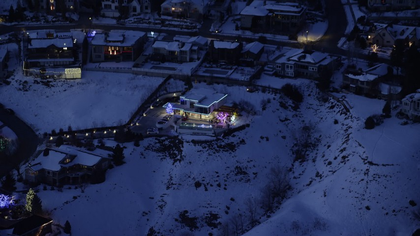 Approach a Home Decorated for Christmas with Winter Snow at Night Aerial Stock Footage | AX128_077