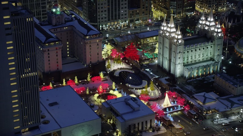 Orbit Fountain and Trees Lit for Christmas at Salt Lake Temple with Snow at Night Aerial Stock Footage | AX128_080