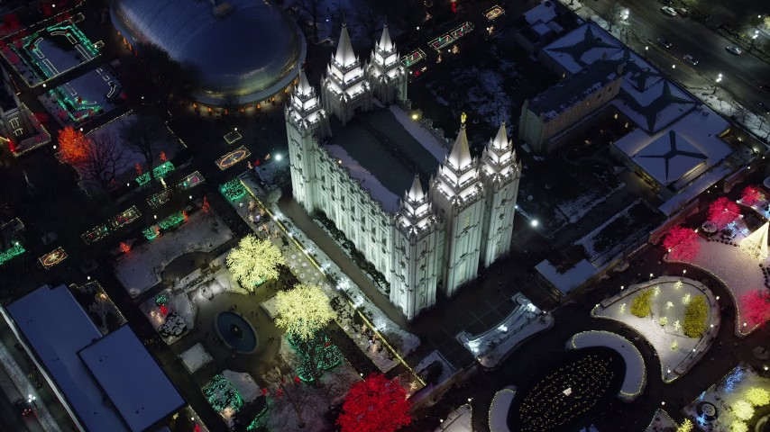 Bird's Eye Orbit of Salt Lake Temple with Colorfully Lit Trees with Winter Snow at Night Aerial Stock Footage | AX128_081
