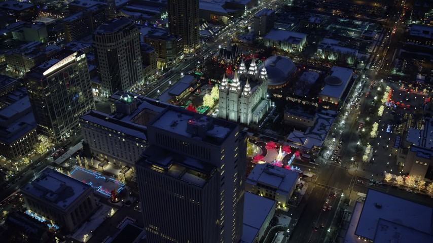 6K stock footage aerial video orbit Church Building by Salt Lake Temple lit for Christmas with winter snow at night, Downtown SLC, Utah Aerial Stock Footage | AX128_085