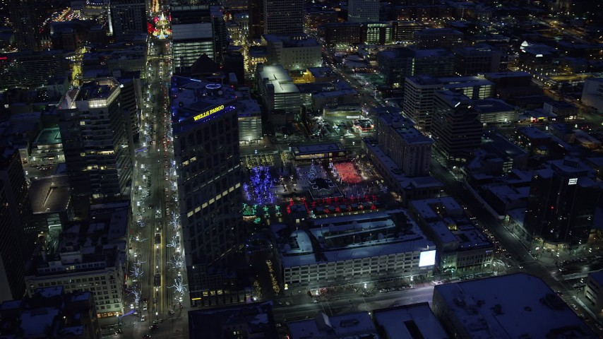 6K stock footage aerial video orbit Wells Fargo Building to reveal Gallivan Center with winter snow at night, Downtown Salt Lake City, Utah Aerial Stock Footage AX128_091 | Axiom Images
