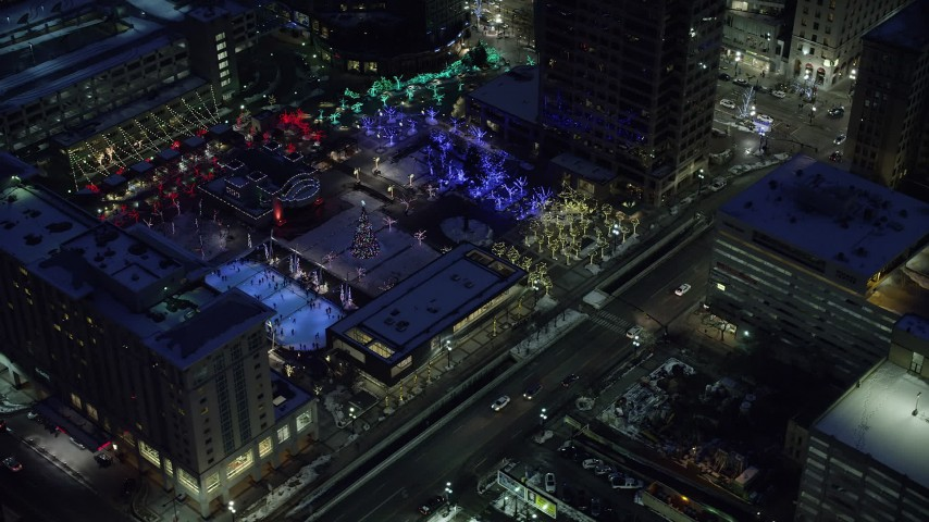 6K stock footage aerial video orbit Christmas tree at Gallivan Center and reveal ice skating rink in winter at night, Downtown Salt Lake City, Utah Aerial Stock Footage | AX128_093