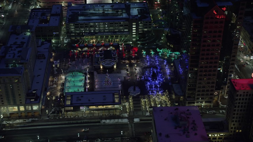Orbit Ice Skating Rink and Christmas Tree at Gallivan Center in Winter at Night Aerial Stock Footage AX128_094
