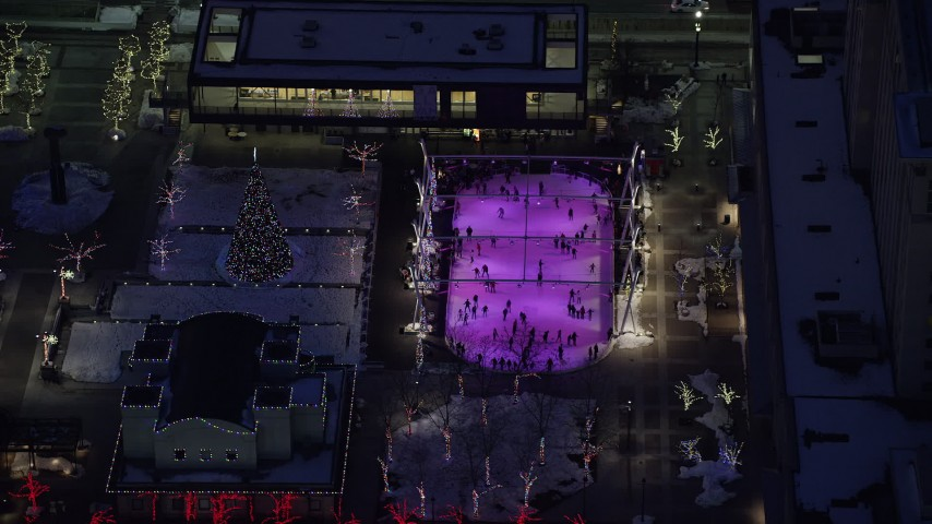 6K stock footage aerial video orbit ice rink and Christmas tree at Gallivan Center with winter snow at night, Downtown Salt Lake City, Utah Aerial Stock Footage | AX128_097
