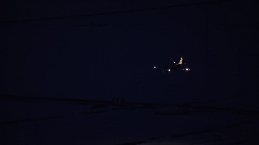 6K stock footage aerial video track jet descending toward the SLC Airport runway for landing at night in winter, Utah Aerial Stock Footage AX128_115 | Axiom Images