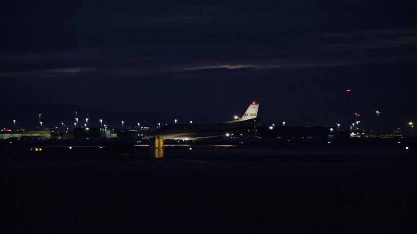 Track Private Jet Taxiing Off Runway at Night in Winter Aerial Stock Footage | AX128_120