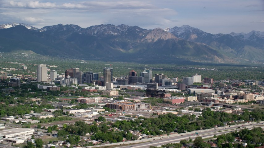 6K stock footage aerial video of flying by the city, Wasatch Range in the distance, Downtown Salt Lake City, Utah Aerial Stock Footage | AX129_004