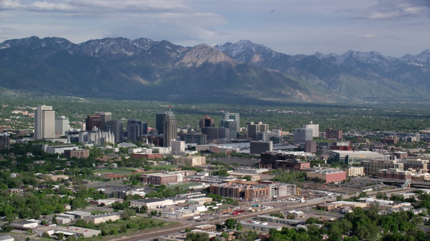 6K stock footage aerial video of flying by city buildings, Wasatch Range in the distance, Downtown Salt Lake City, Utah Aerial Stock Footage | AX129_005