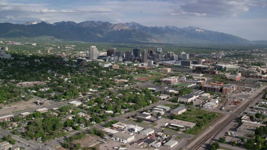 Flying by buildings, neighborhoods, sports fields, Downtown Salt Lake City, Utah Aerial Stock Footage | AX129_006