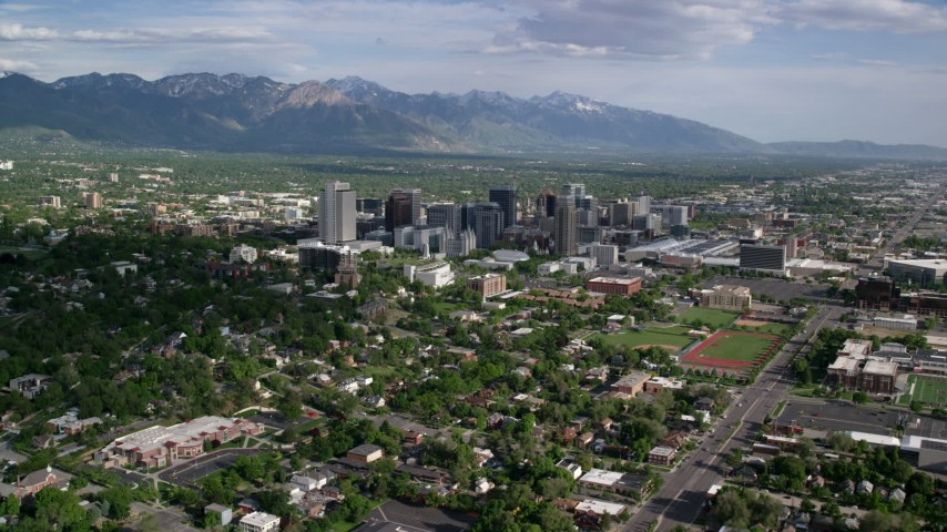 6K stock footage aerial video of flying by the city's buildings, neighborhoods, sports fields, Downtown Salt Lake City, Utah Aerial Stock Footage   AX129_007