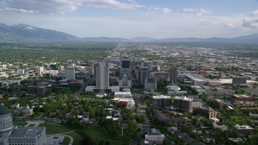Flying by buildings, Utah State Capitol Dome, Downtown Salt Lake City, Utah Aerial Stock Footage | AX129_009