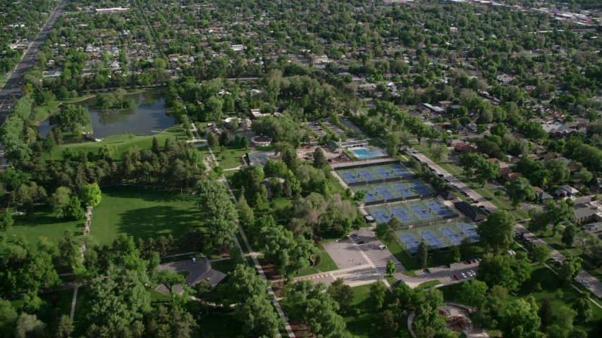 6K stock footage aerial video of flying over Liberty Park, tennis courts, approaching suburbs, Salt Lake City, Utah Aerial Stock Footage | AX129_022