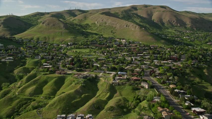 6K stock footage aerial video of flying by suburban neighborhood, Wasatch Range foothills, Salt Lake City, Utah Aerial Stock Footage | AX129_058