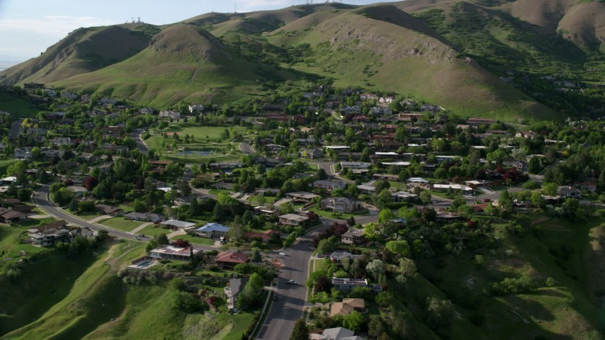 6K stock footage aerial video of flying by hilltop suburban neighborhood, Wasatch Range, Salt Lake City, Utah Aerial Stock Footage | AX129_059