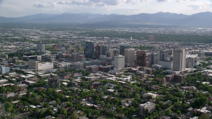 6K stock footage aerial video of flying by city buildings, distant Oquirrh Mountains, Downtown Salt Lake City, Utah Aerial Stock Footage | AX129_060