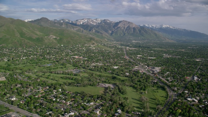 6K stock footage aerial video fly over suburban neighborhoods, approach the Wasatch Range, Salt Lake City, Utah Aerial Stock Footage | AX129_081