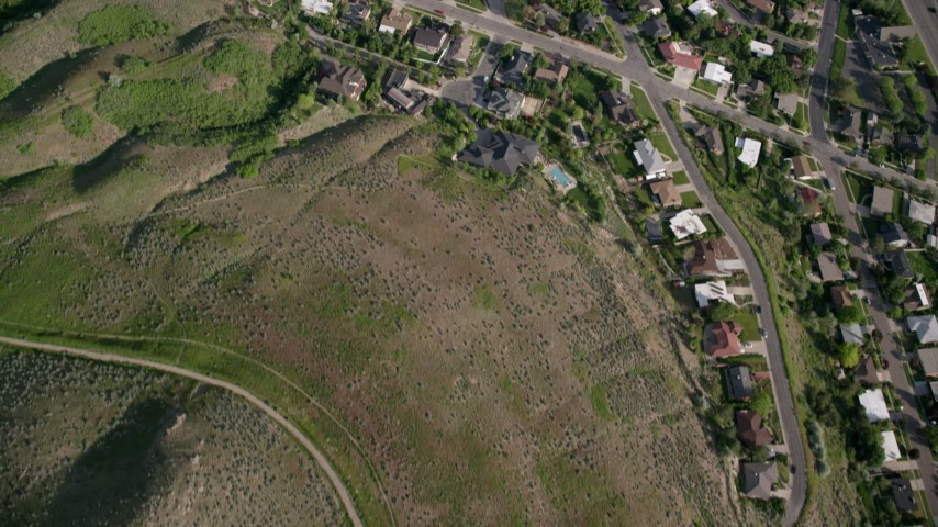 6K aerial stock footage video bird's eye view over suburban neighborhoods, green foothills, Salt Lake City, Utah Aerial Stock Footage | AX129_085