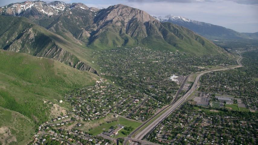 Approaching suburban neighborhoods, Wasatch Range, Salt Lake City, Utah Aerial Stock Footage | AX129_089
