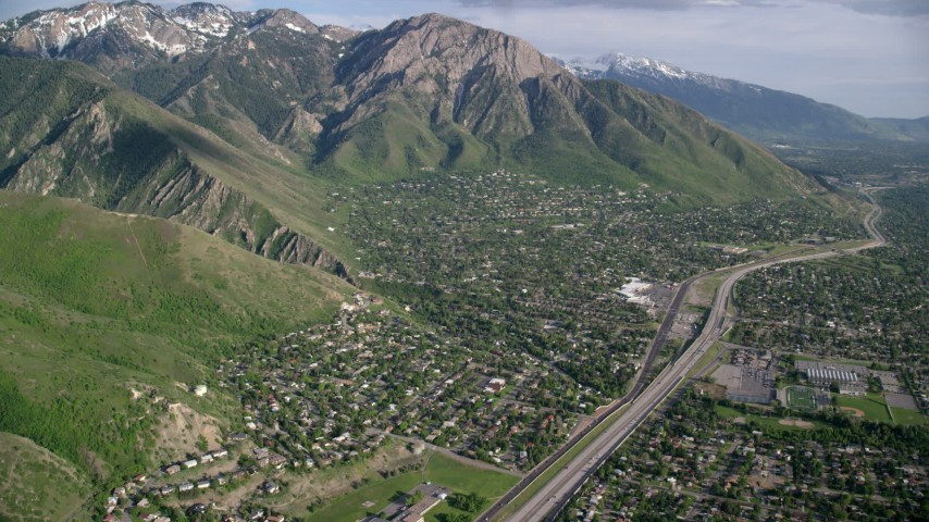 Approaching suburban neighborhoods, Wasatch Range, Salt Lake City, Utah Aerial Stock Footage | AX129_089