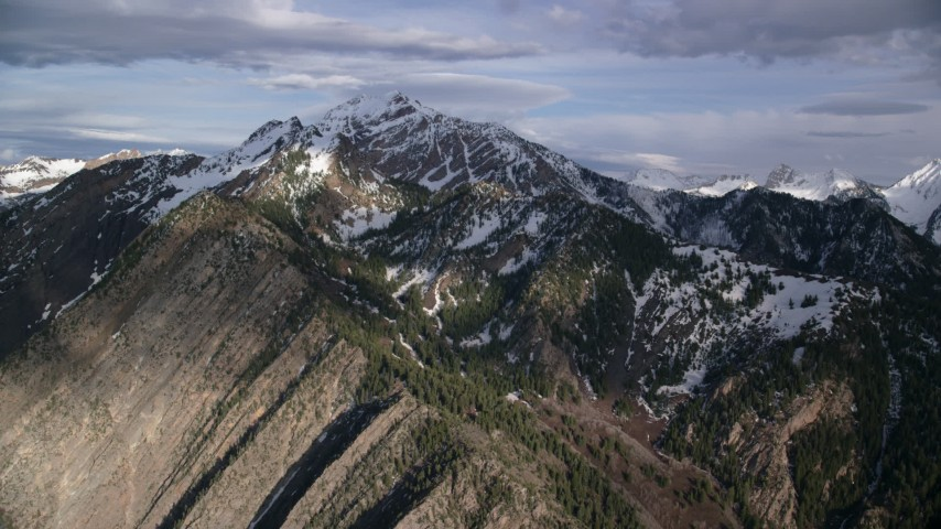 6K stock footage aerial video of flying by the snow-capped peaks of the Wasatch Range, Utah Aerial Stock Footage | AX129_103