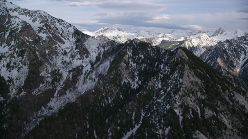 6K stock footage aerial video pass by the snow-covered peaks in the Wasatch Range, Utah Aerial Stock Footage | AX129_106