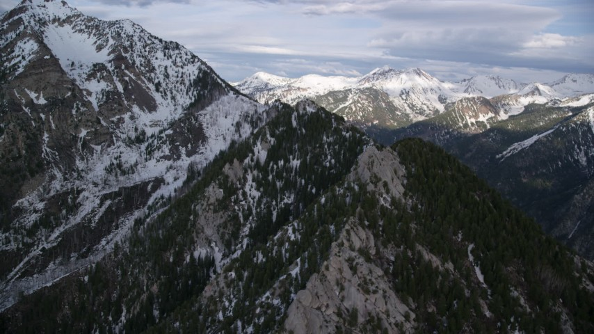 Flying by snow-capped peaks and ridges of the Wasatch Range, Utah Aerial Stock Footage   AX129_107