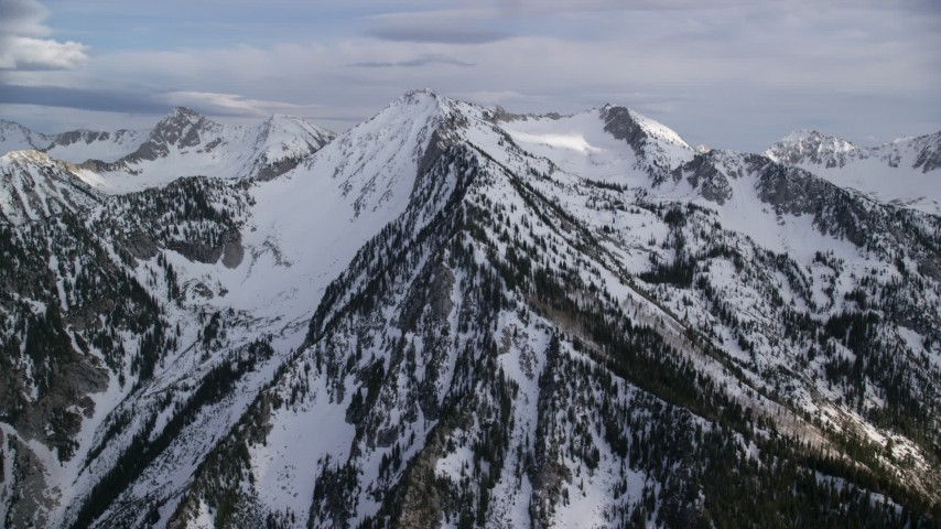 6K stock footage aerial video of an approach to snow-covered ridges, peaks, Wasatch Range, Utah Aerial Stock Footage | AX129_111