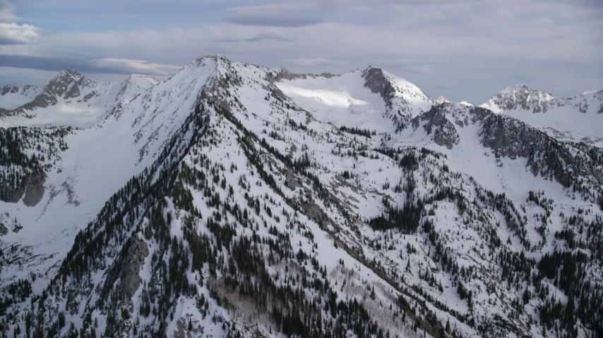 6K stock footage aerial video of flying toward snow-covered peaks, ridges, Wasatch Range, Utah Aerial Stock Footage | AX129_112