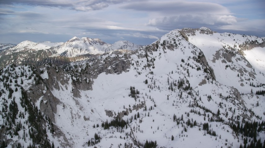 Flying by snow-covered peaks and ridges, Wasatch Range, Utah Aerial Stock Footage | AX129_113