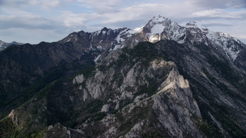 Flying by lightly snow-capped mountain peak, Wasatch Range, Utah Aerial Stock Footage | AX129_130