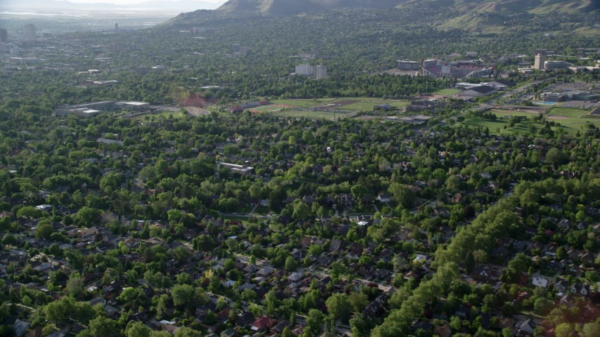 Fly over suburbs, approach University of Utah sports fields, Salt Lake City, Utah Aerial Stock Footage | AX129_141