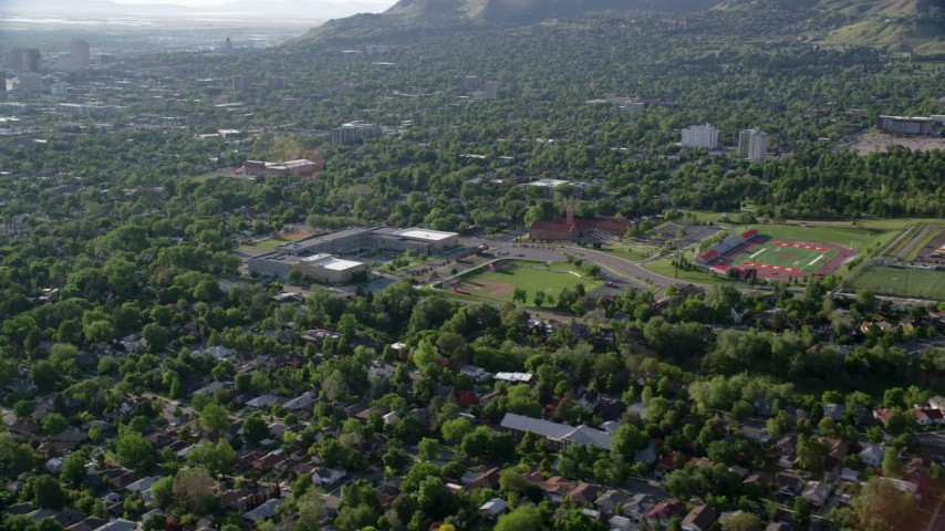 6K stock footage aerial video fly over suburbs to approach University of Utah sports fields, Salt Lake City, Utah Aerial Stock Footage | AX129_142