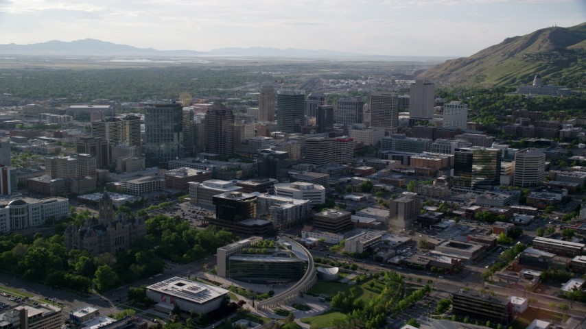 6K stock footage video of flying by city buildings, pan to Utah State Capitol, Downtown Salt Lake City, Utah Aerial Stock Footage | AX129_145