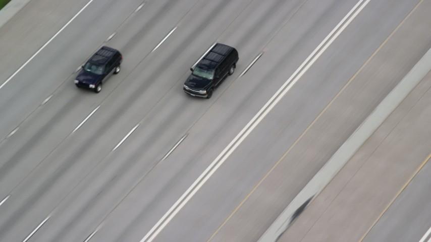 Tracking SUVs on Interstate 15, light traffic, Salt Lake City, Utah Aerial Stock Footage   AX130_015
