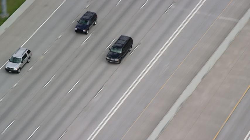Tracking a black SUV on Interstate 15, light traffic, Salt Lake City, Utah Aerial Stock Footage | AX130_016