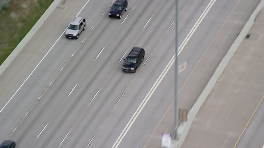 6K aerial stock footage video of tracking a black SUV passing light traffic on I-15, Salt Lake City, Utah Aerial Stock Footage | AX130_016