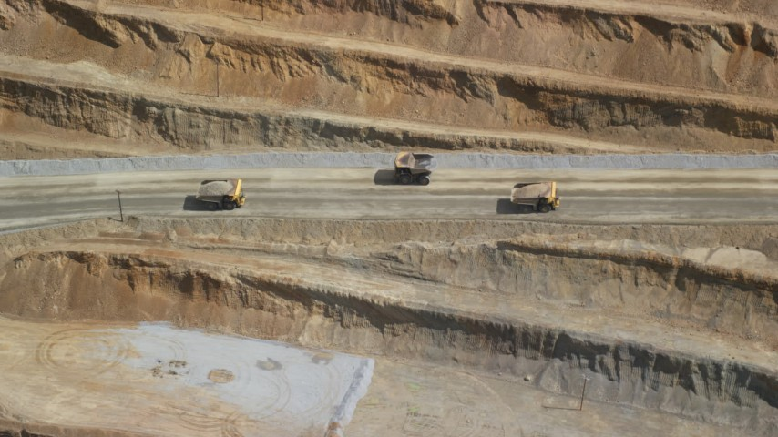 6K stock footage aerial video of flying by gravel haulers in Kennecott Copper Mine, aka Bingham Canyon Mine, Utah Aerial Stock Footage | AX130_054
